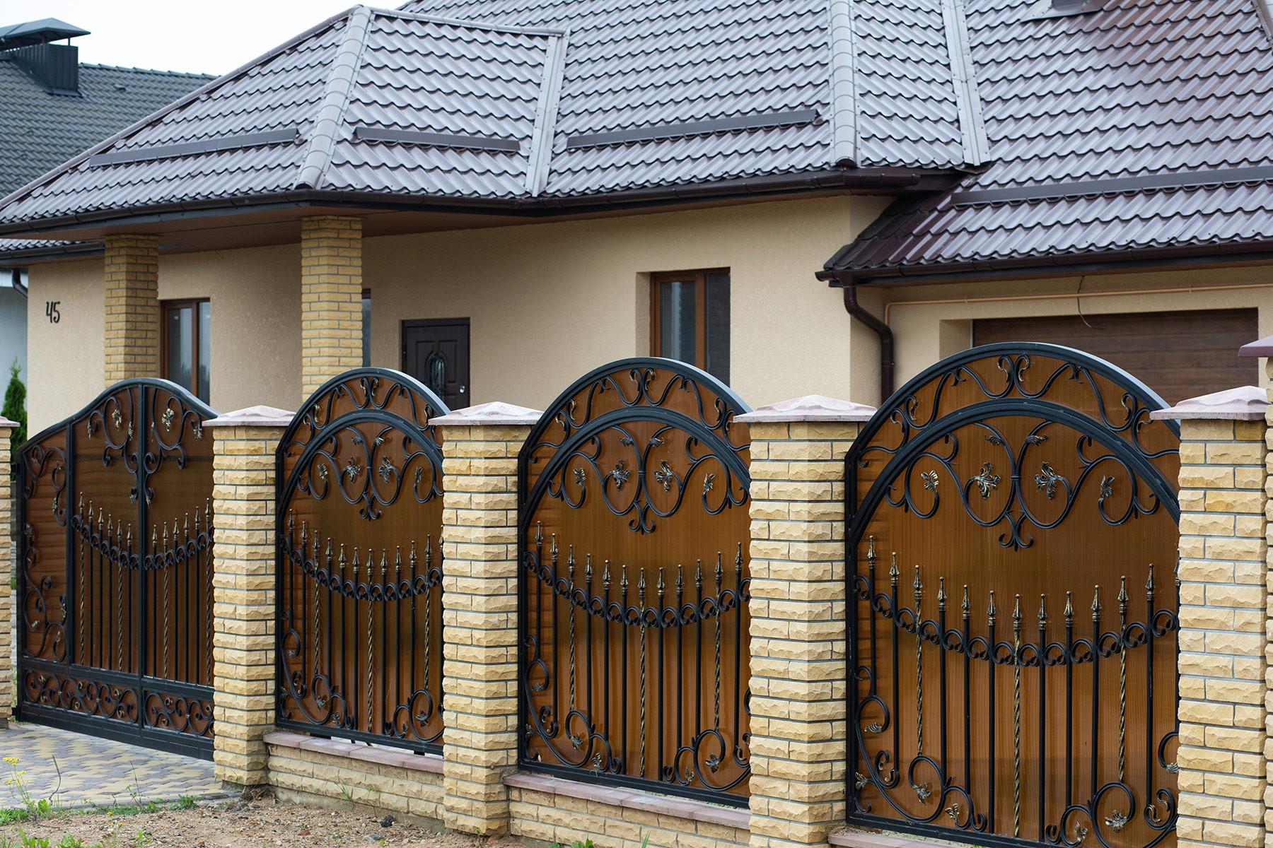 Кованный забор из желтого рустированного кирпича